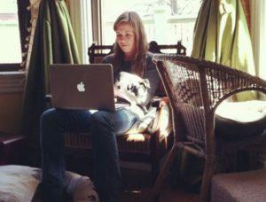 アーロンの愛犬:ビーンをお膝に、PCをさわるローラ・キンドレッド 典拠: instagram